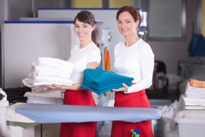 Women with folded clothing front of washing machines